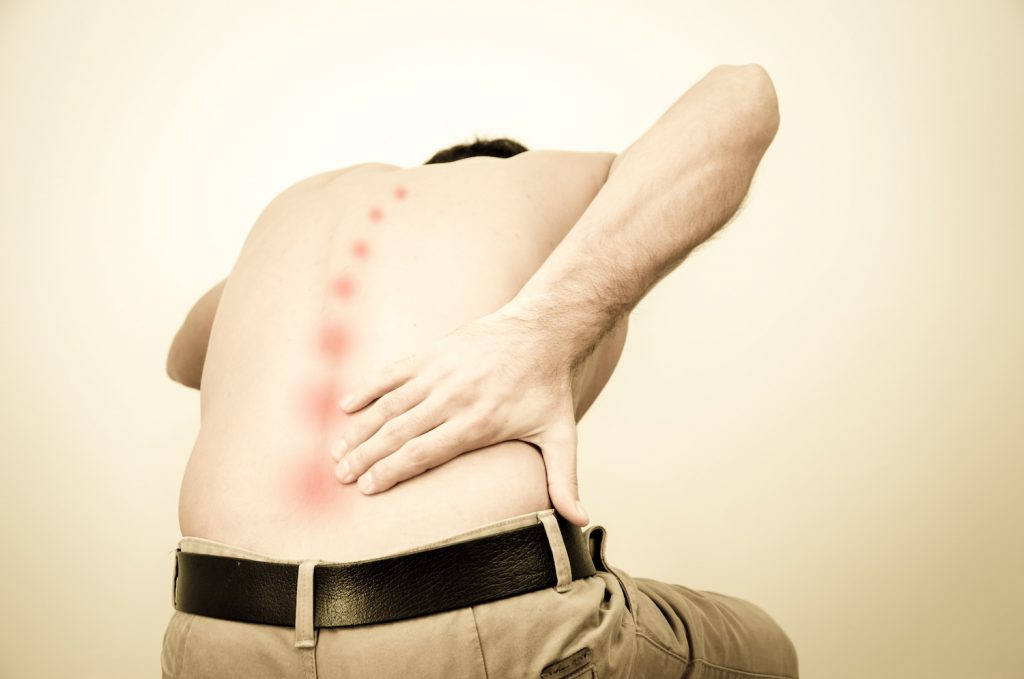 man bent over grabbing lower back in pain