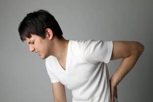 side profile of man in white t-shirt hunched over with back pain