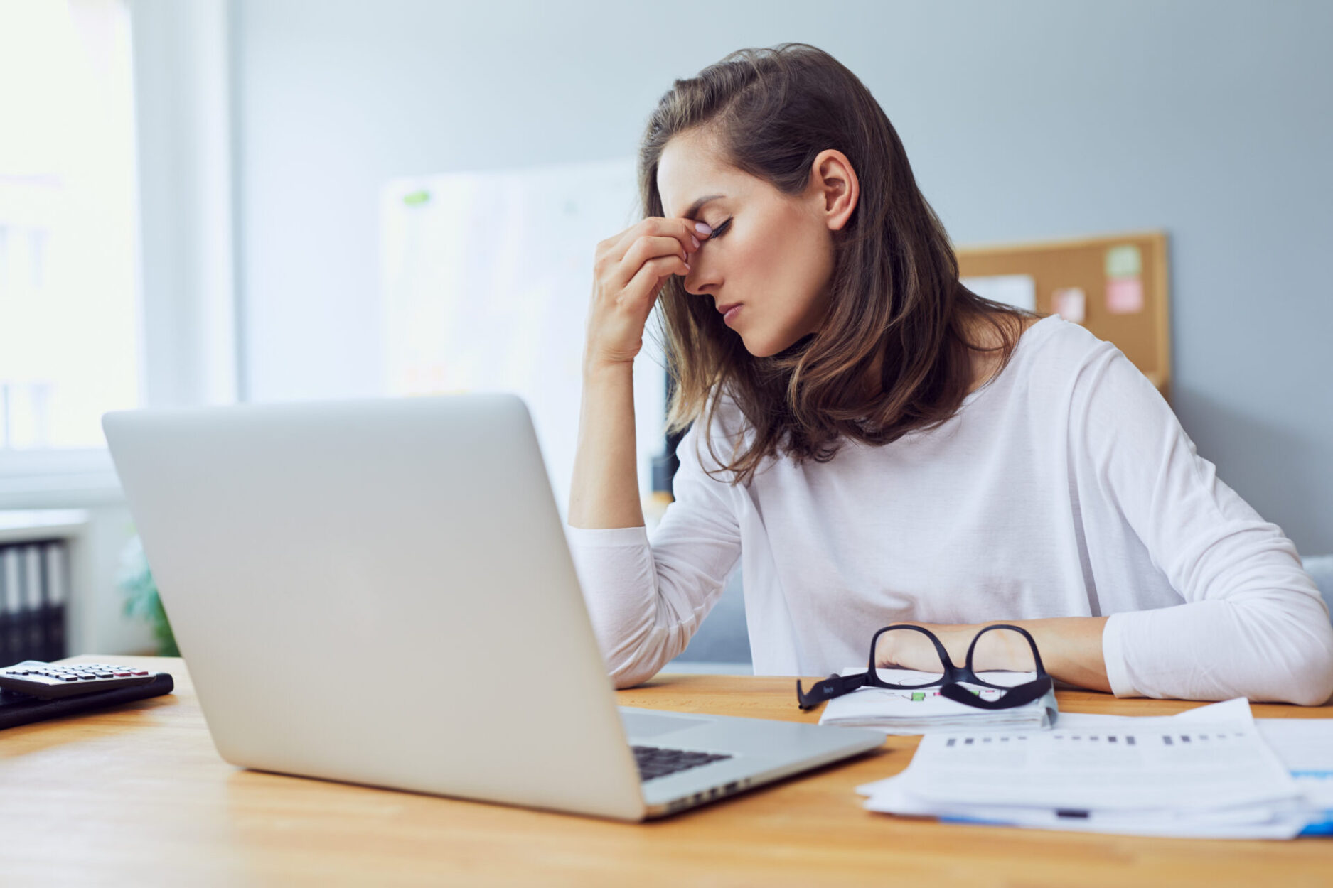 woman sitting at desk in front of laptop with eyes closed