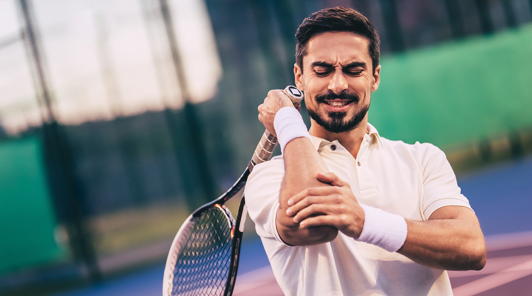 man on tennis court with racket in hand grabbing elbow in pain