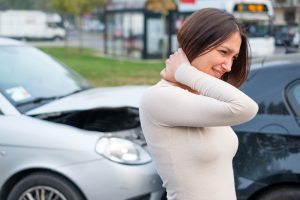 woman standing next to car accident grabbing neck
