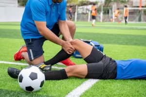 soccer player laying on ground while coach inspects injured knee