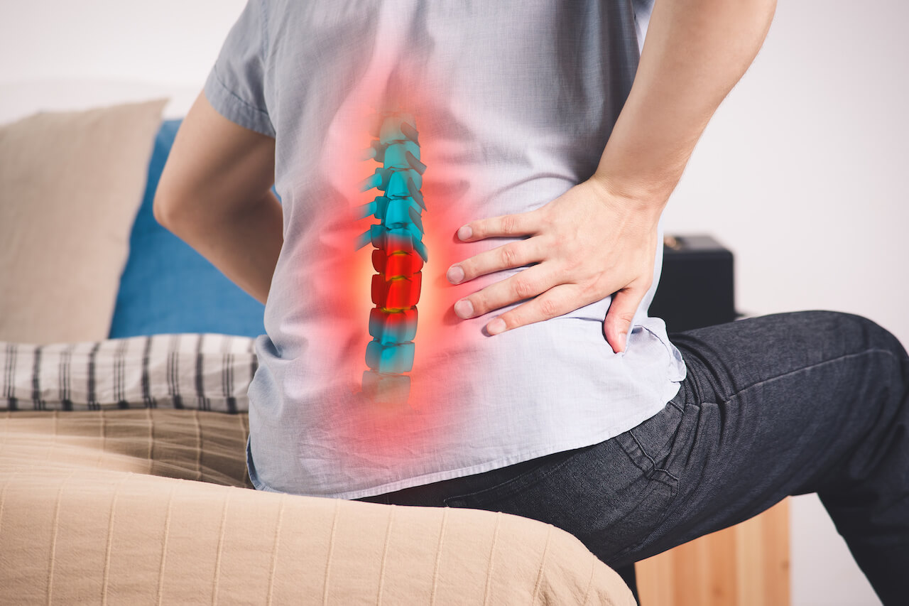 back of man sitting on bed with spine graphic overlay indicating back pain