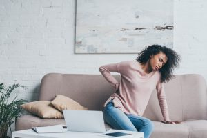 woman sitting on couch rubbing lower back in pain