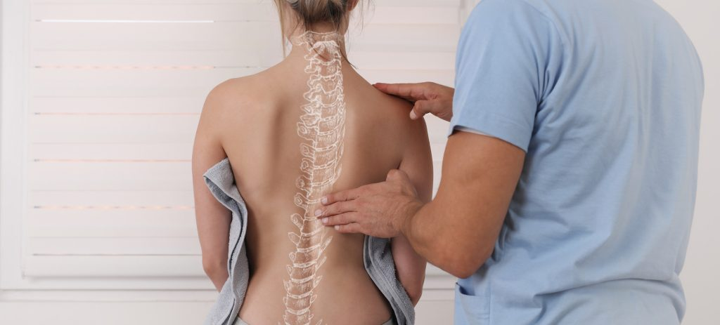 chirpractor touching back of female patient with overlay of spine on her back