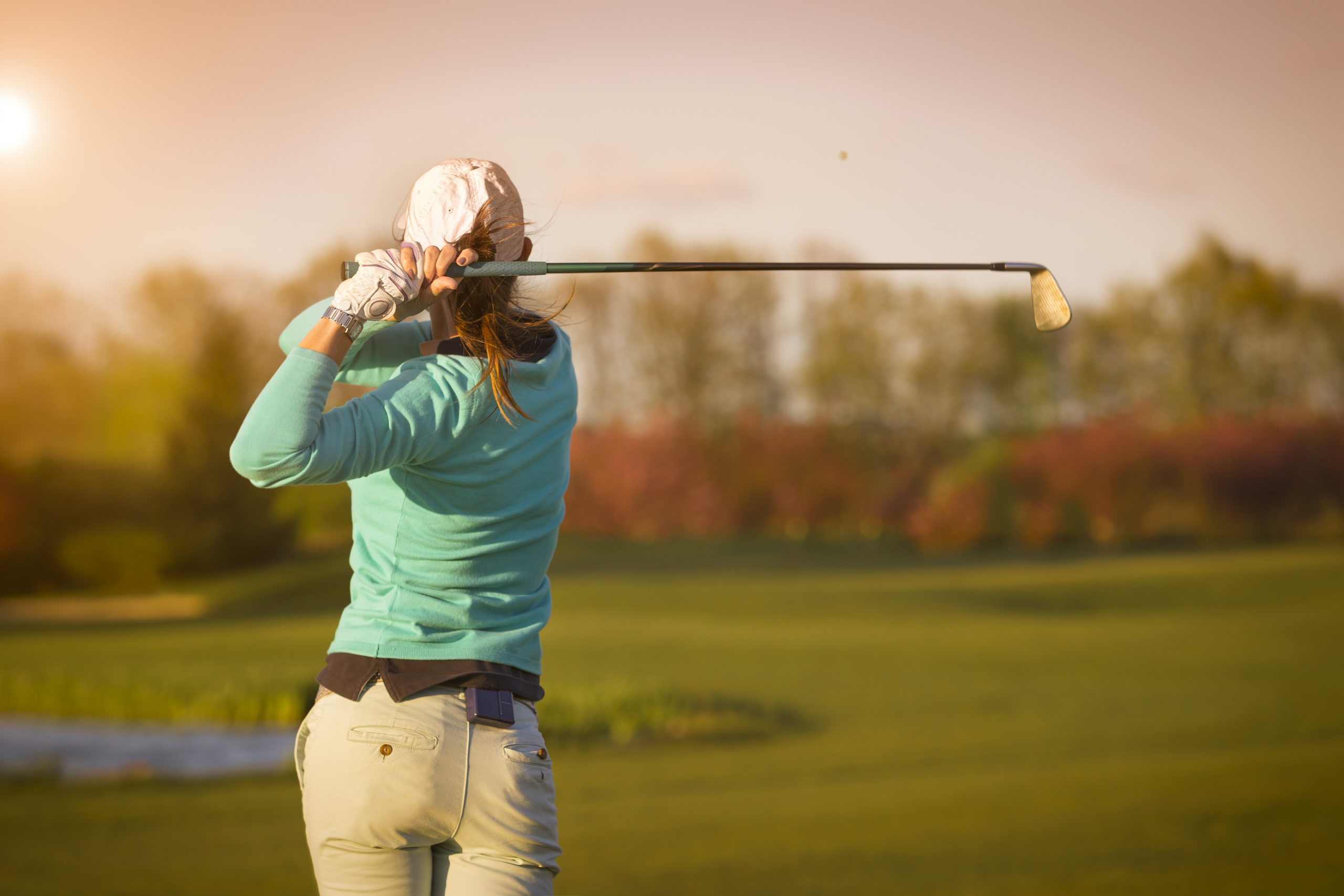 woman on golf course after swinging her club