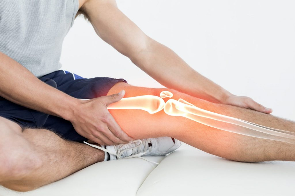 man on floor grabbing leg with graphic overlay of knee joint shown