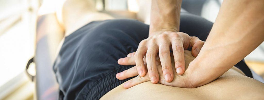 therapist working on male patient's lower back