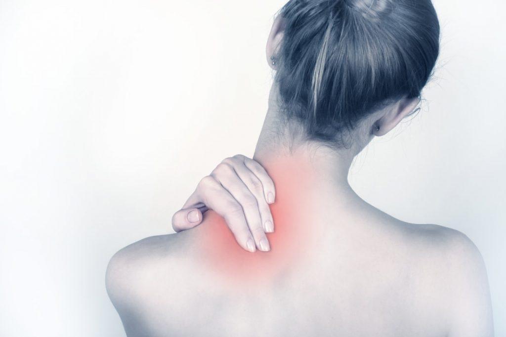 back of woman grabbing her shoulder and neck