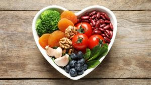heart shaped bowl filled with fruits, nuts, beans and vegetables