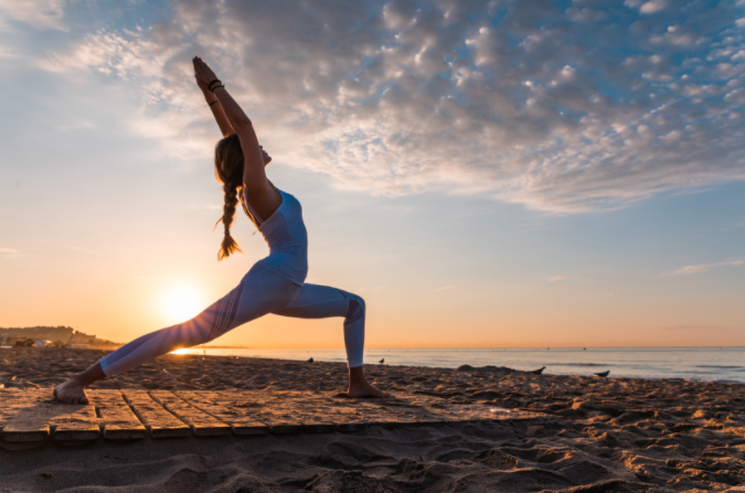 woman doing yoga on the beach at sunset